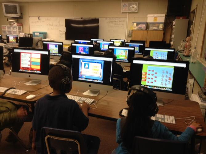 Primary students navigating Apple computers in the lab.